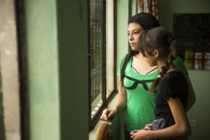 Image shows a mother and daughter looking out a barred window