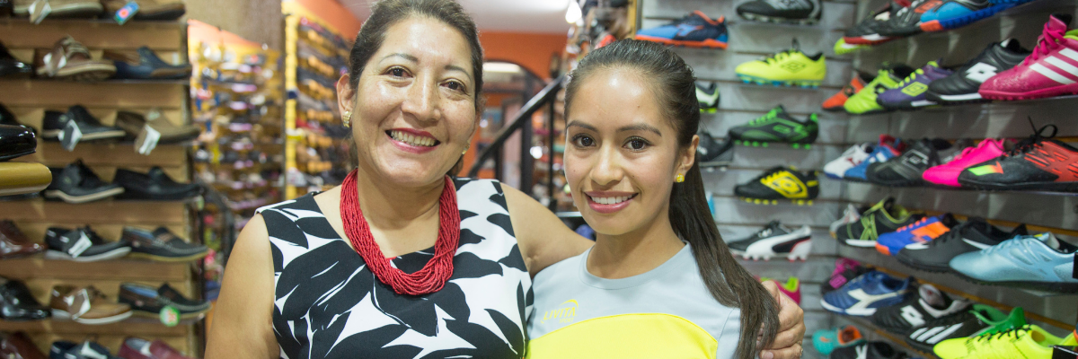 Images shows a mother and daughter smiling and standing in their shoe store