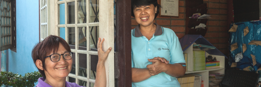 Image shows two women standing by a door and smiling at the camera