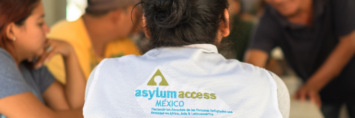 Image shows a member of Asylum Access Mexico staff from behind wearing a white shirt with the organization logo