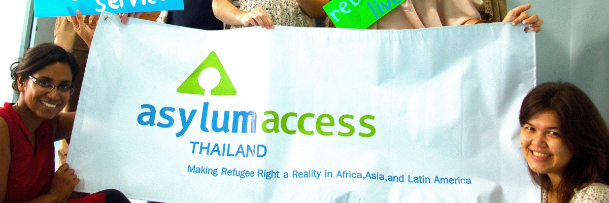 Image shows two people smiling and holding up an Asylum Access Thailand banner